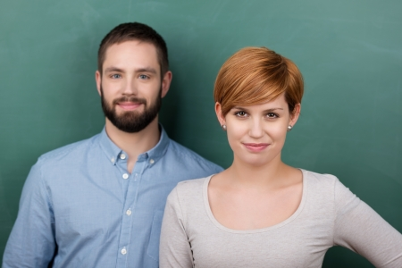 educator: Portrait of confident male and female students against chalkboard Stock Photo