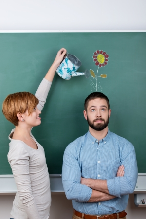 Side view of woman holding watering can over mans head with flower drawn on chalkboard representing growth photo