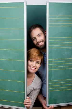 Portrait of happy male and female students hiding behind green panels photo