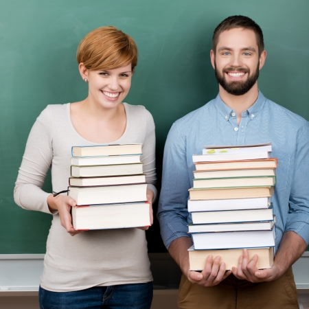 Portrait of confident male and female teachers carrying stack of books against chalkboard photo