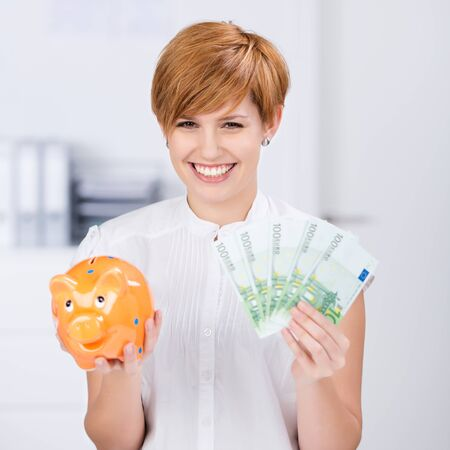 red hair woman: Portrait of happy businesswoman holding Euro notes and piggybank in office