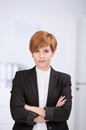 woman short hair: Portrait of confident businesswoman with arms crossed standing in office