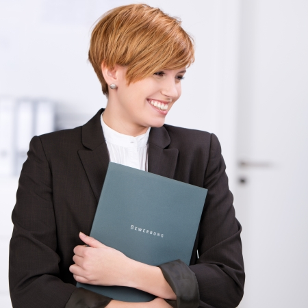 Young businesswoman with a curriculum vitae in her arms, looking for a job photo
