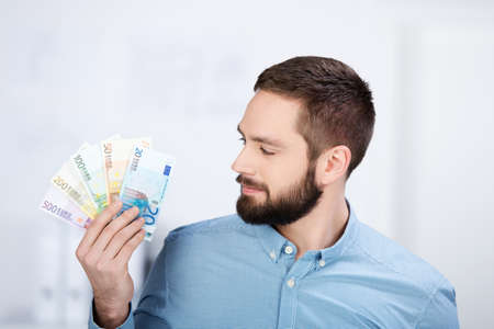 win money: Portrait of smiling businessman holding Euro notes in office