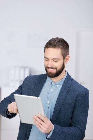 Young businessman using digital tablet in office photo