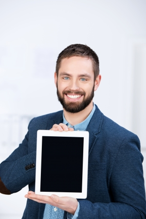 Portrait of happy young businessman showing digital tablet in office photo