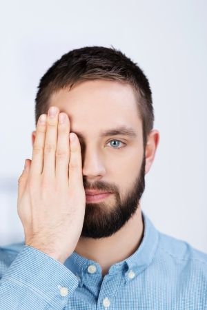 one eye: Closeup portrait of young businessman covering his one eye with hand in office Stock Photo
