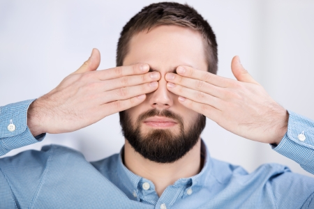 Closeup of young businessman covering his eyes with hands in office Stock Photo