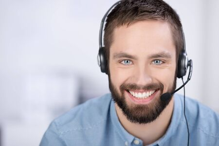 closeup of happy young customer service executive communicating on headset in office photo