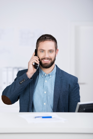 business reception: Young businessman using mobile phone at desk in office