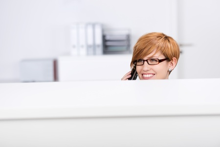 Beautiful young woman looking away while on call in office\ cubicle