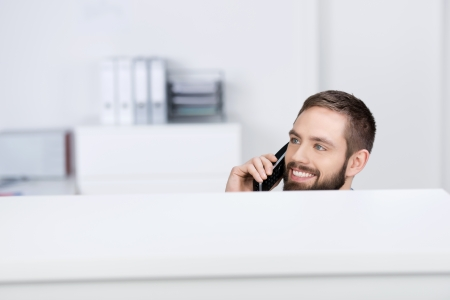cubicle: Happy young businessman looking away while on call in office cubicle Stock Photo