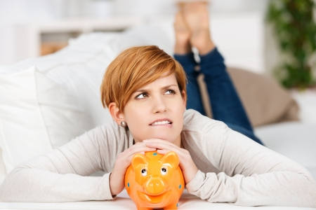 Portrait of thinking woman with piggy bank while lying on sofa at home photo