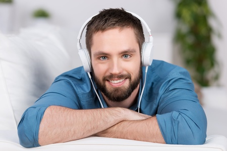 Portrait of happy young man lying on sofa while listening to music in house Stock Photo - 21109808
