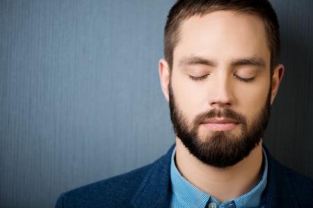 Close-up van knappe zakenman met gesloten ogen tegen blauwe achtergrond