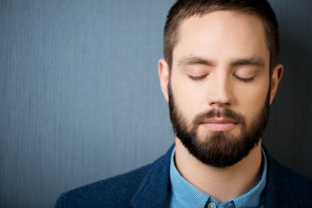 ojos cerrados: Primer plano de apuesto hombre de negocios con los ojos cerrados contra el fondo azul