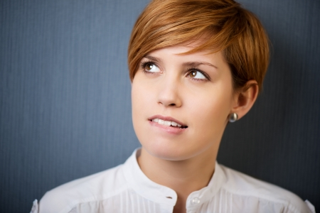 Doordachte jonge zakenvrouw wegkijken geïsoleerde over blauwe achtergrond