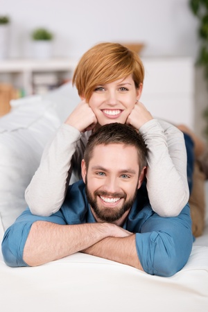 red sofa: Couple Relaxing On Sofa At Home Smiling At Camera