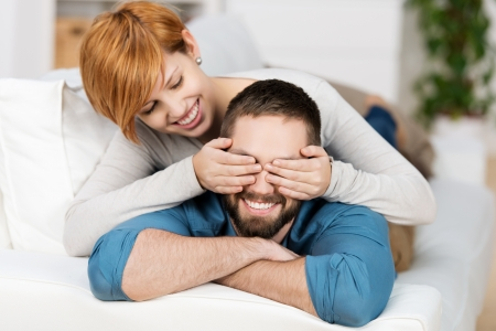 hand covering eye: Happy young woman covering mans eyes while lying on sofa
