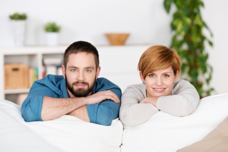 Young smiling couple is resting on sofa photo