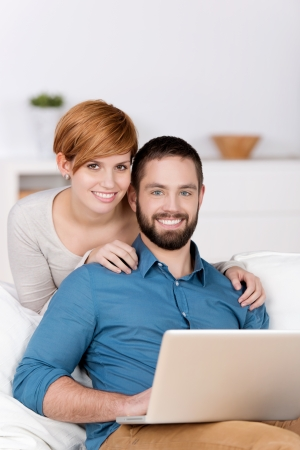 Portrait of happy young couple with laptop in house photo
