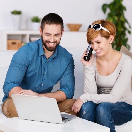 persona llamando: Una pareja de jóvenes hablando a una oficina de reservas y compras de la red