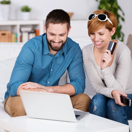 house shopping: Portrait of happy couple shopping online with credit card in house Stock Photo