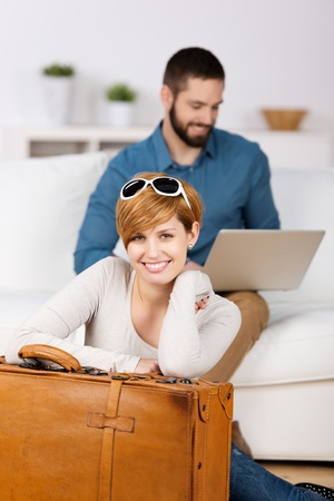 Portrait of happy young woman with suitcase and man using laptop at home photo