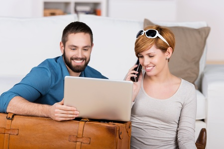 front: Happy couple shopping online with phone and laptop Stock Photo