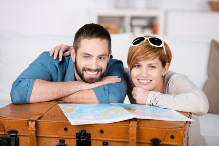 Portrait of happy couple with map leaning on suitcase in house