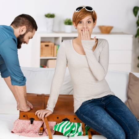 Happy young couple trying to close suitcase at home photo