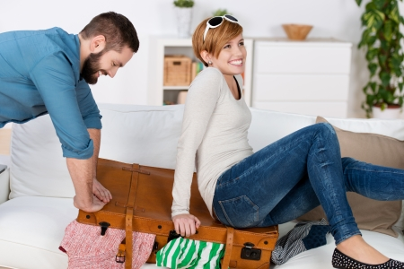 closing: Happy young couple trying to close suitcase at home