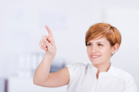 Young businesswoman pointing while looking away in office photo