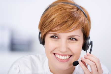 red telephone: closeup of happy female customer service executive speaking on headset in office Stock Photo