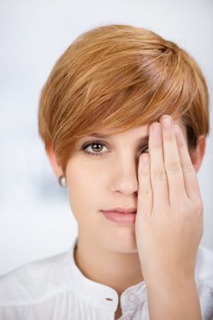 one eye: closeup portrait of businesswoman covering her one eye with hand in office Stock Photo