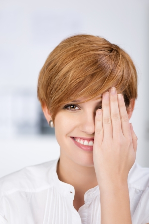 hand covering eye: Closeup portrait of happy businesswoman covering her one eye with hand in office