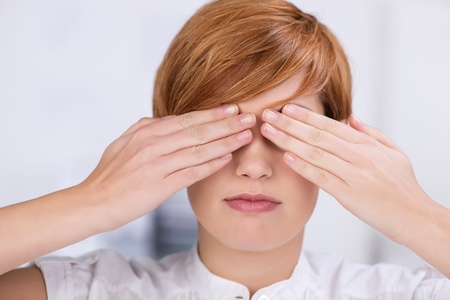 obscured face: Closeup of young businesswoman covering eyes with hands in office Stock Photo
