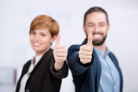 Portrait of happy businessman and businesswoman showing thumbs up sign in office photo