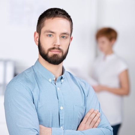 businessman pondering documents: Portrait of confident young businessman with female coworker reading document in background at office
