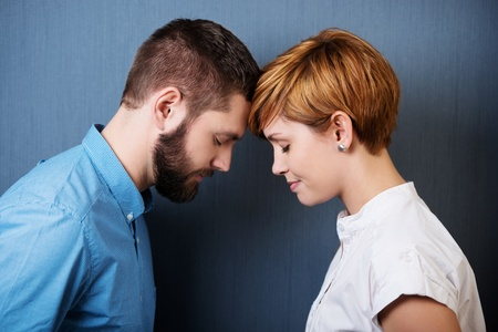 Beautiful couple face to face with closed eyes, blue background photo