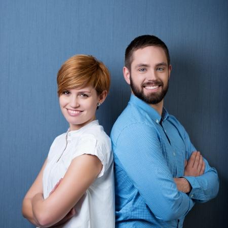 Sonriendo gente de negocios espalda con espalda con fondo azul Foto de archivo - 21110042