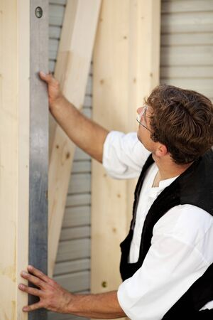 Carpenter measures with a water level tool photo
