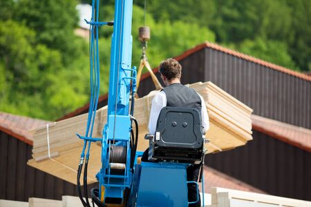 Carpenter at work with a crane to lift heavy wood panels photo
