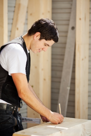 woodworker: Young carpenter is marking a piece of wood