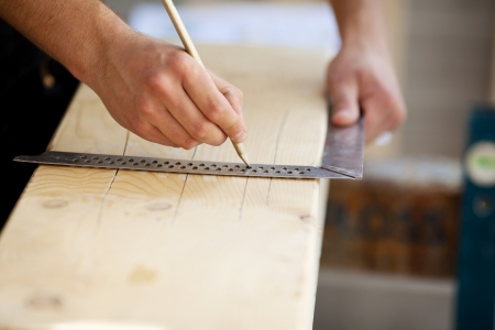 Carpenter making marks on a wooden beam photo
