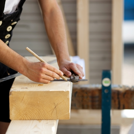 Construction worker marks a piece of wood photo
