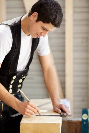 woodworker: Young construction worker marks a piece of wood Stock Photo