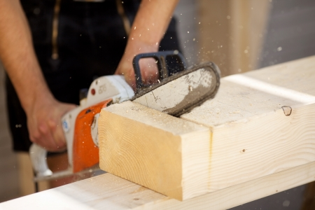 wood shavings: Carpenter is sawing a wood beam with tool