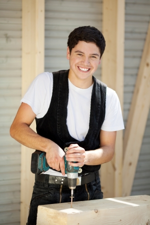 Smiling young carpenter enjoys doing his job photo