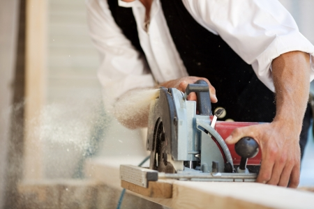 Close-up of a carpenter working with a circular saw photo